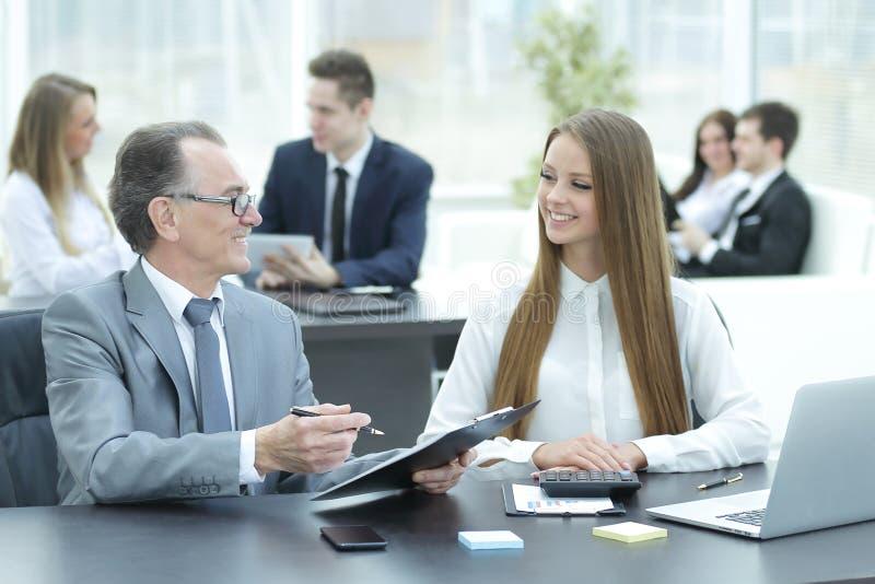 Vendedor e gestor de equipa que trabalham com cartas de papel imagens de stock royalty free