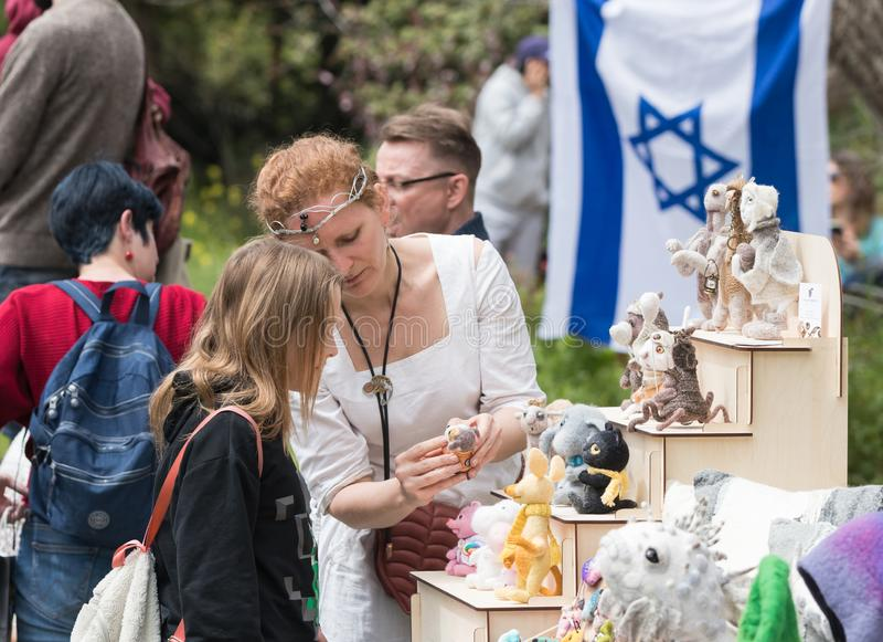 Vendedor - el participante del festival muestra a visitante un juguete hecho a mano en el festival de Purim con rey Arthur en la  imagen de archivo libre de regalías