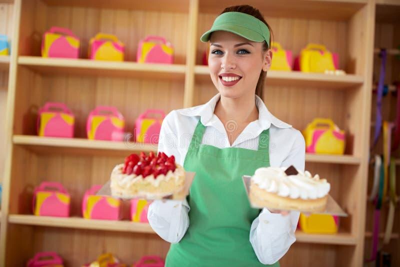 Vendedor em bolos agradáveis da posse dois da loja de pastelaria nas mãos imagens de stock royalty free