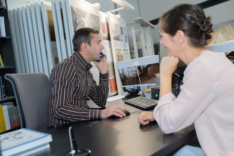 Vendedor en el teléfono mientras que el cliente espera imagen de archivo
