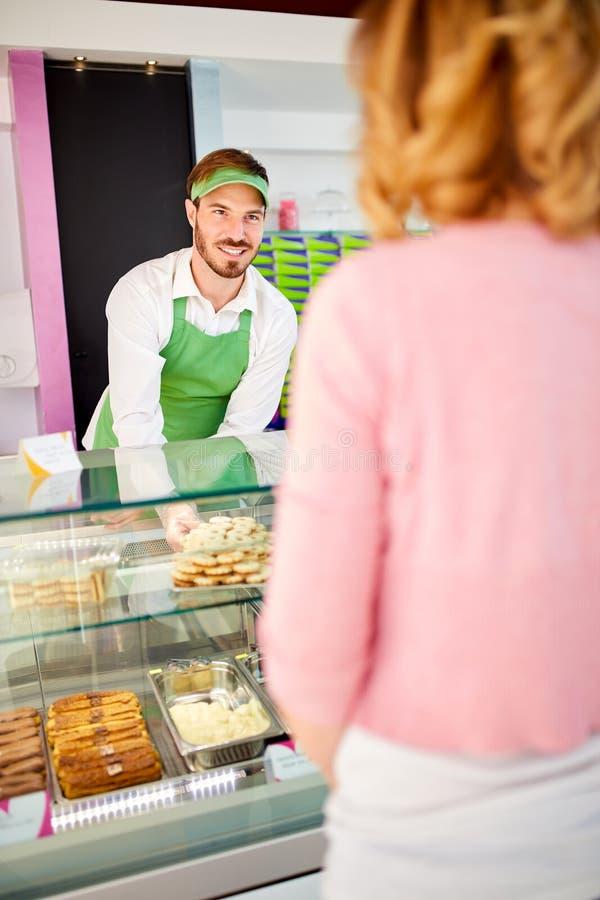 Vendedor en la tienda de pasteles que asiste a la mujer imágenes de archivo libres de regalías