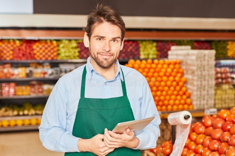 Vendedor en un supermercado con ordenador foto de archivo