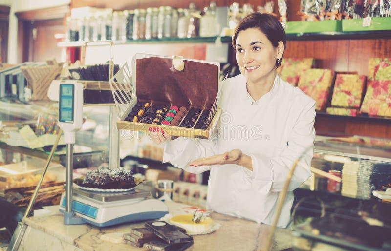 Vendedor fêmea que oferece a grande caixa dos chocolates imagens de stock