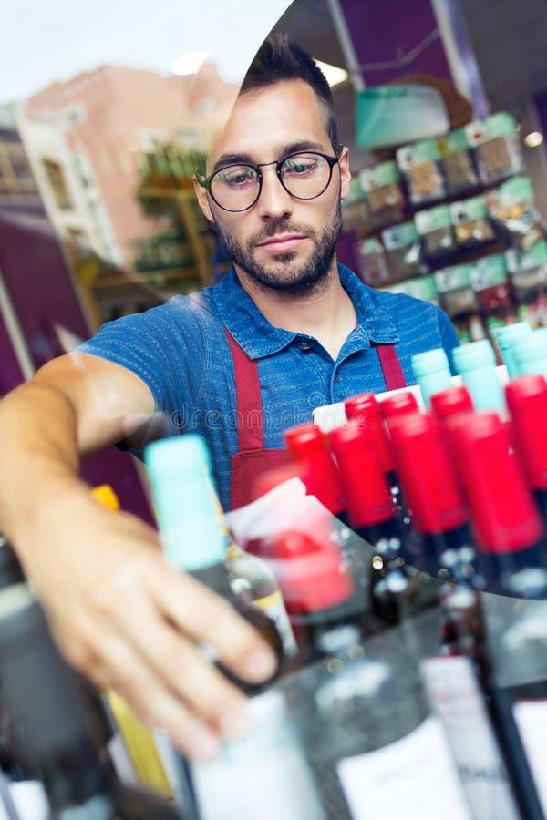 Vendedor hermoso joven que selecciona una botella de vino en tienda de ultramarinos de la salud foto de archivo