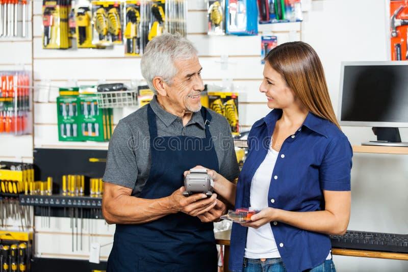 Vendedor Holding Electronic Reader mientras que cliente fotos de archivo