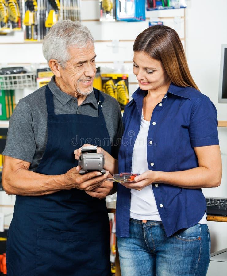 Vendedor Holding Electronic Reader mientras que cliente fotografía de archivo