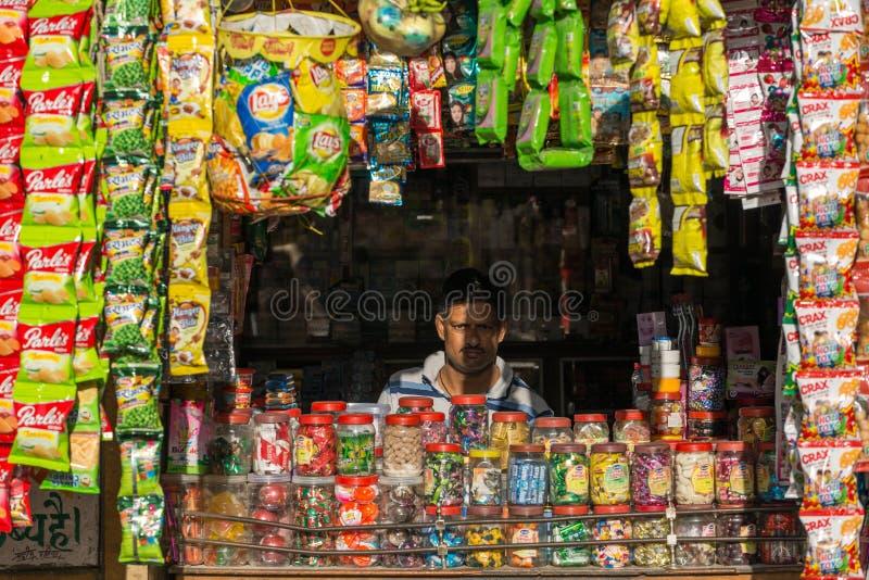 Vendedor indio no identificado que mira de su tienda de la calle en Jaisalmer, la India fotos de archivo libres de regalías