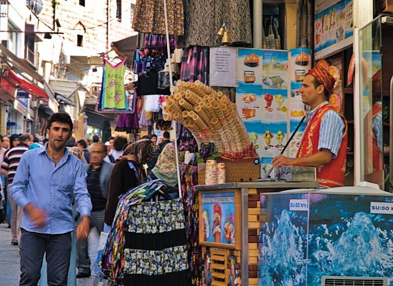 Vendedor joven del helado del dondurma vestido en traje turco tradicional en tienda de alimentos de la calle y foto de archivo