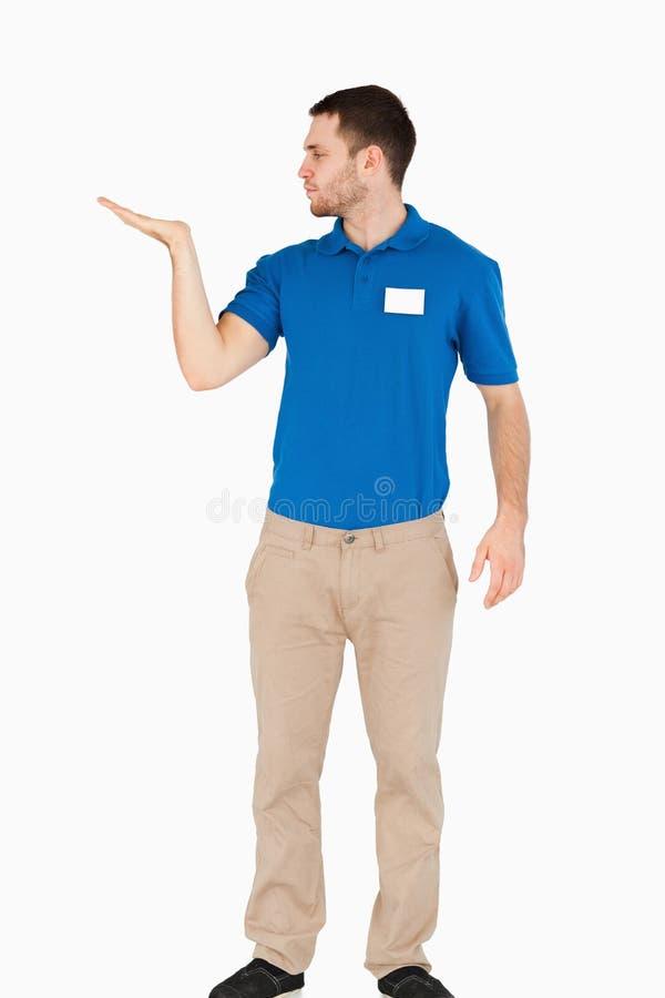 Vendedor joven que presenta en su palma fotografía de archivo