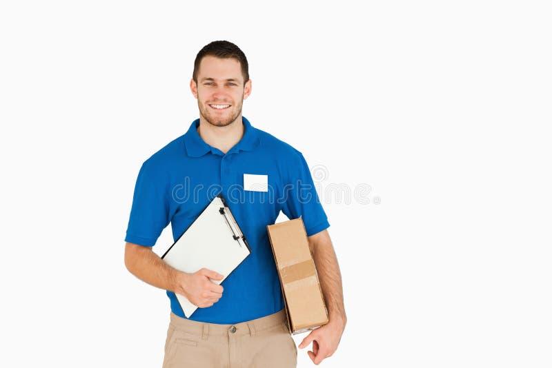 Vendedor joven sonriente con el paquete y el sujetapapeles fotografía de archivo libre de regalías