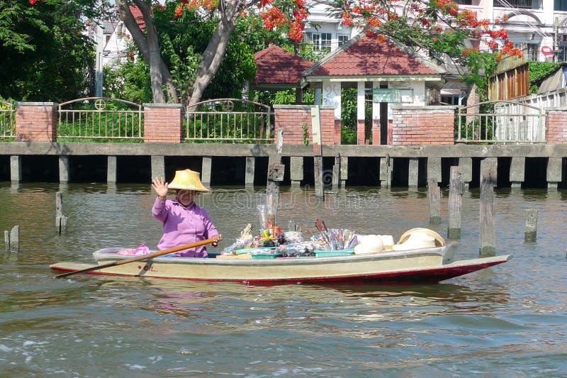 Vendedor local que vende bens em canais de Banguecoque em Tailândia imagens de stock
