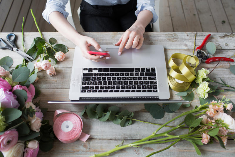 Vendedor maduro de sorriso de Small Business Flower do florista da mulher Está usando seus telefone e portátil para tomar ordens  imagens de stock royalty free
