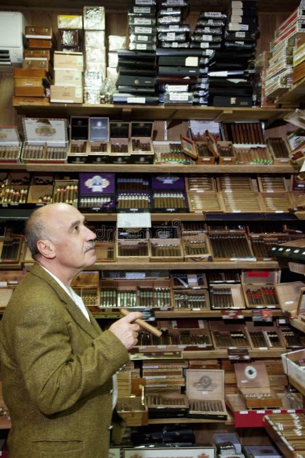 Vendedor maduro do cigarro que olha charutos na exposição fotos de stock royalty free