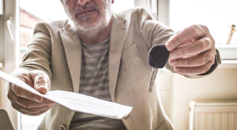 Vendedor maduro que da llave y documentos del coche Cierre para arriba imagen de archivo