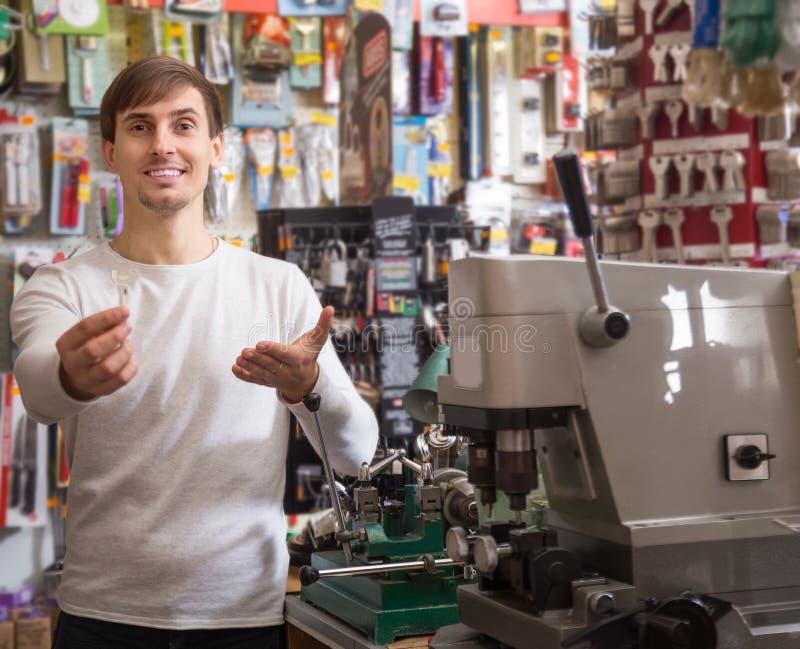 Vendedor masculino novo que levanta com chave imagem de stock