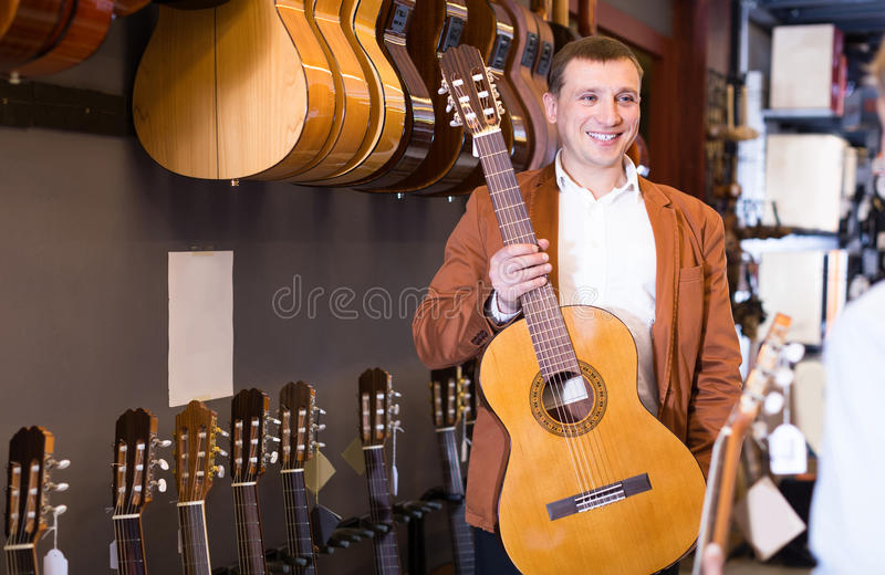 Vendedor masculino que mostra a guitarra acústica ao cliente do menino no sho musical foto de stock royalty free