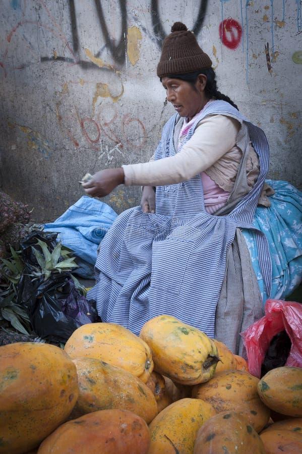 Vendedor no identificado de la mujer de la calle que lleva la ropa tradicional en el mercado local de Rodriguez, vendiendo las fr imagen de archivo