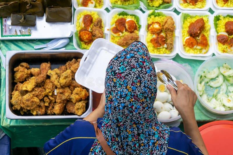 Vendedor no identificado preparando el paquete de arroz amarillo en el puesto de comida en el mercado de alimentos de la ciudad de fotos de archivo