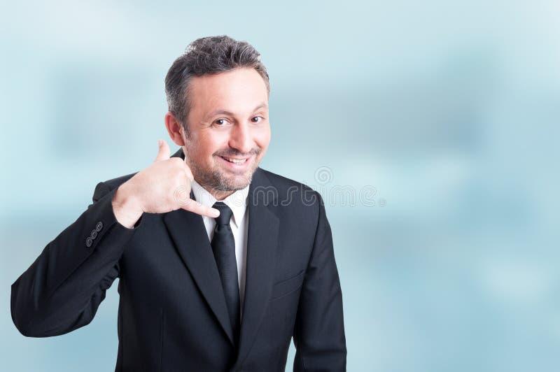 Vendedor novo alegre que faz uma chamada mim gesto com mão foto de stock