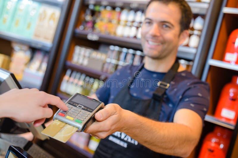 Vendedor novo entusiástico feliz receber o pagamento do cliente fotos de stock royalty free