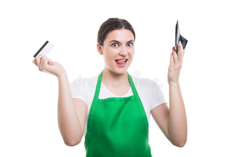 Vendedor novo entusiasmado que guarda o cartão e a carteira de crédito fotografia de stock royalty free