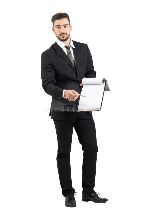 Vendedor novo no terno que aponta o espaço da assinatura com contrato de oferecimento do lápis imagens de stock