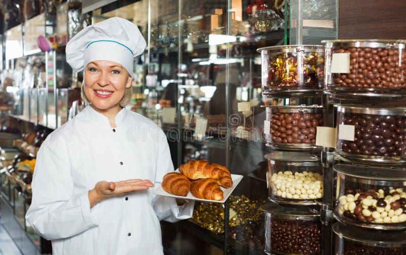 Vendedor positivo sonriente con confectio oscuro y blanco de los chocolates imagen de archivo libre de regalías