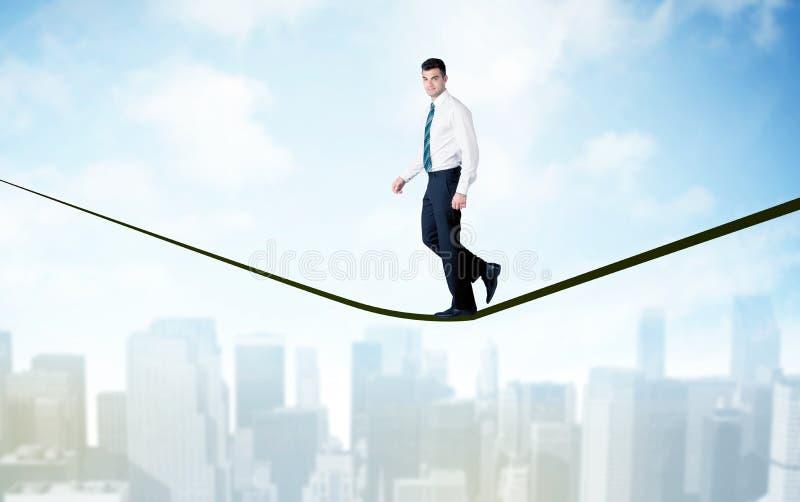 Vendedor que anda na corda acima da cidade foto de stock