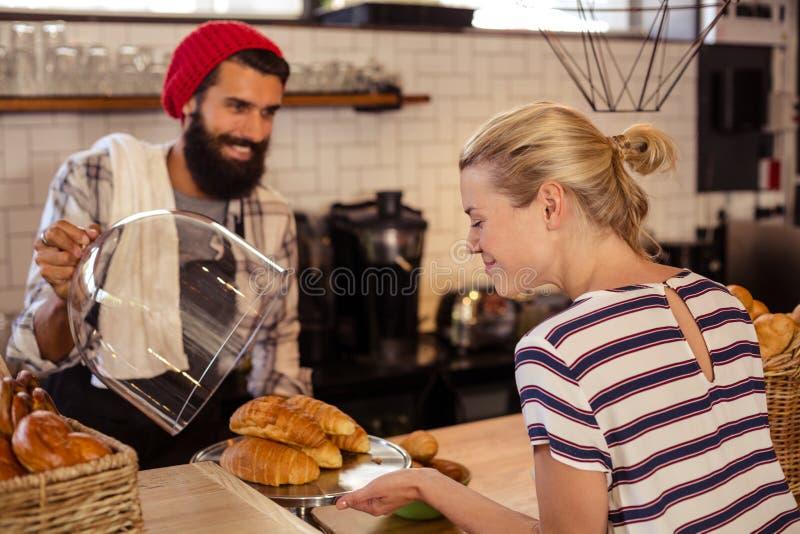 Vendedor que apresenta croissant a um cliente fotografia de stock royalty free