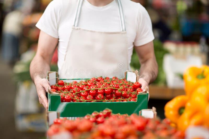 Vendedor que celebra el tomate de cereza en el mercado callejero foto de archivo