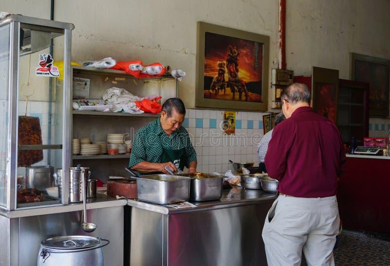 Vendedor que cocina en el restaurante chino imagen de archivo
