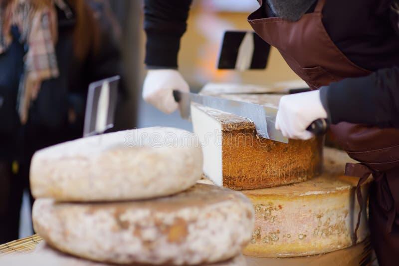 Vendedor que corta o queijo orgânico no mercado do fazendeiro em Strasbourg, França r foto de stock