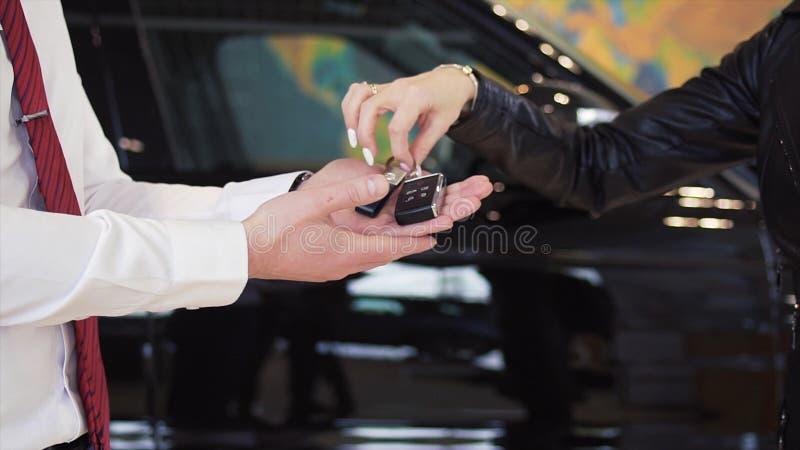 Vendedor que dá a chave do carro ao cliente interno estoque O concessionário automóvel dá chaves do carro a uma mulher imagens de stock