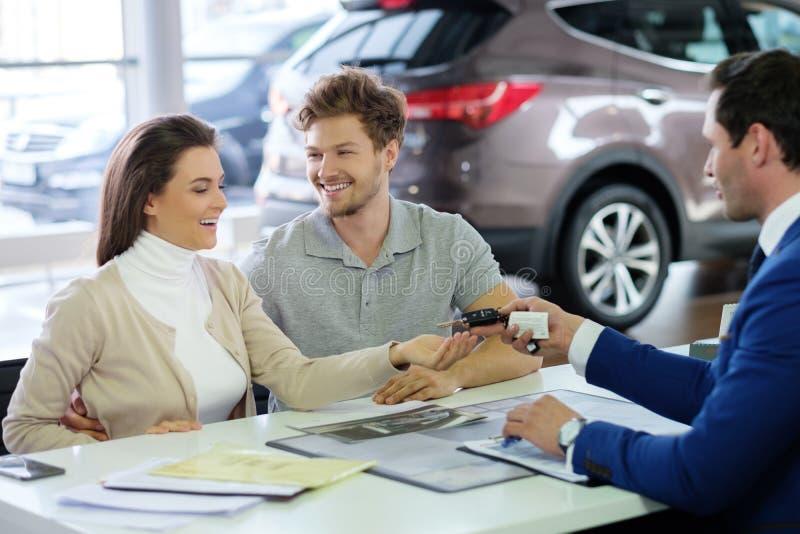 Vendedor que dá a chave do carro novo a um par novo na sala de exposições do negócio imagens de stock