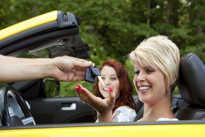 Vendedor que dá a cliente chaves novas do carro fotografia de stock