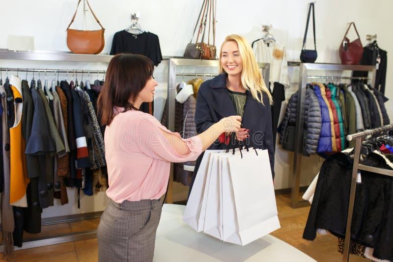 Vendedor que dá sacos de compras para o cliente foto de stock