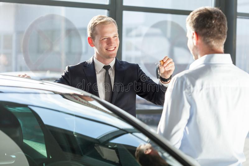 Vendedor que da llave del coche imagen de archivo libre de regalías