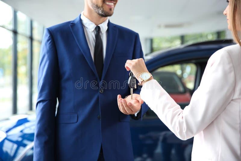 Vendedor que da llaves del coche para servir en la representación auto fotografía de archivo
