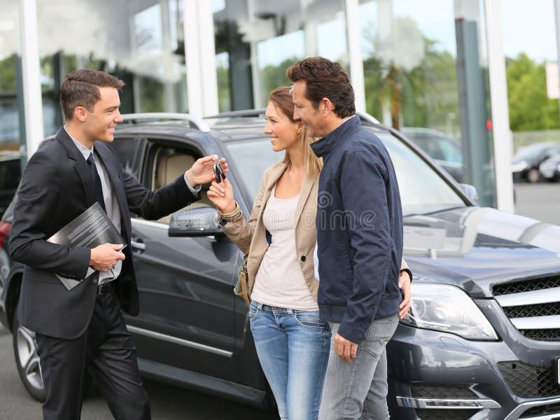 Vendedor que da llaves del nuevo coche a los clientes felices foto de archivo