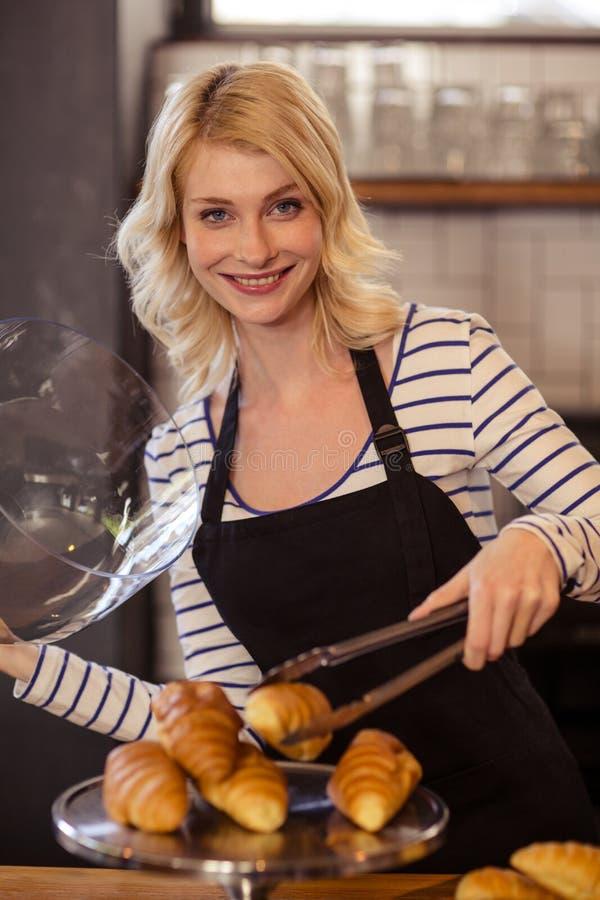 Vendedor que escolhe um croissant com tenazes de brasa imagens de stock