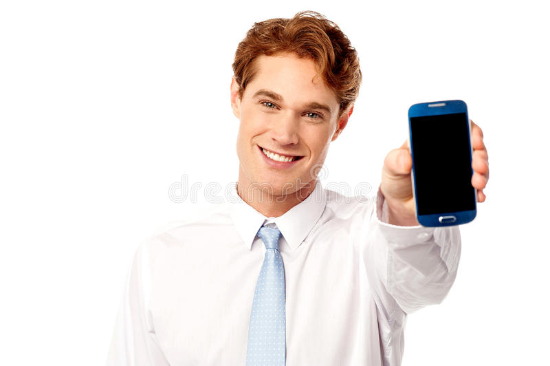 Vendedor que exhibe el móvil nuevamente lanzado foto de archivo