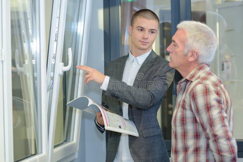 Vendedor que exhibe ventanas esmaltadas doble imagenes de archivo