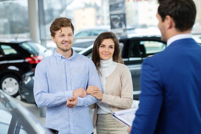 Vendedor que fala a um par novo na sala de exposições do negócio imagens de stock