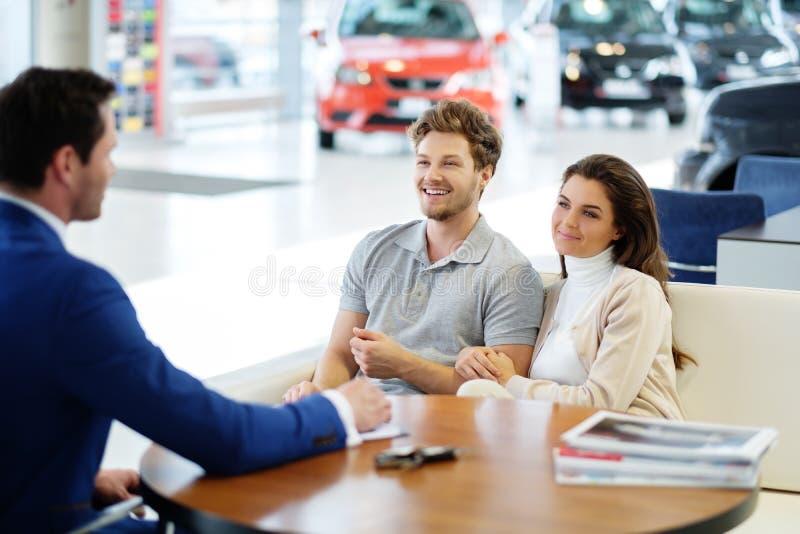 Vendedor que habla con un par joven en la sala de exposición de la representación imagenes de archivo