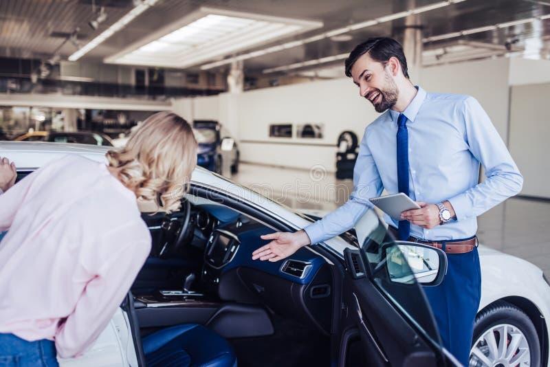 Vendedor que mira el nuevo coche con la mujer imagenes de archivo