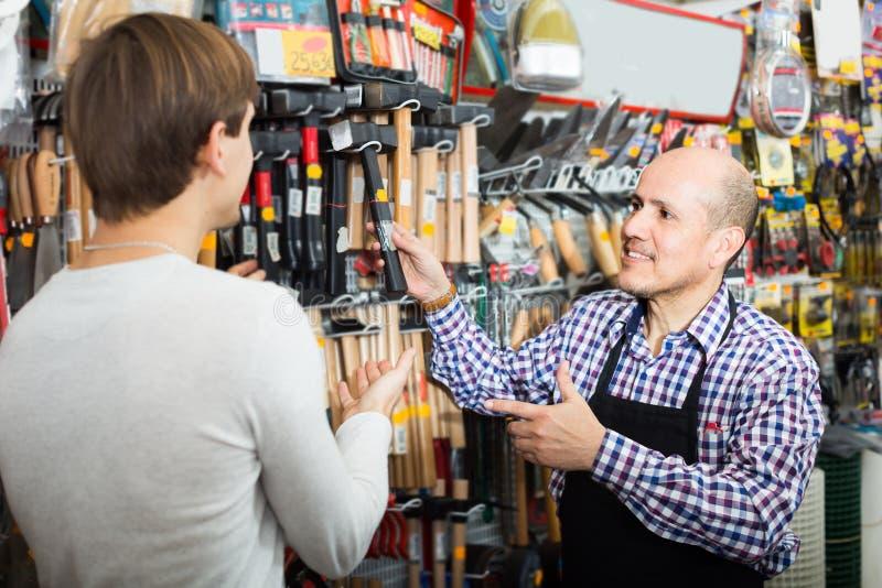 Vendedor que mostra ferramentas diferentes imagens de stock