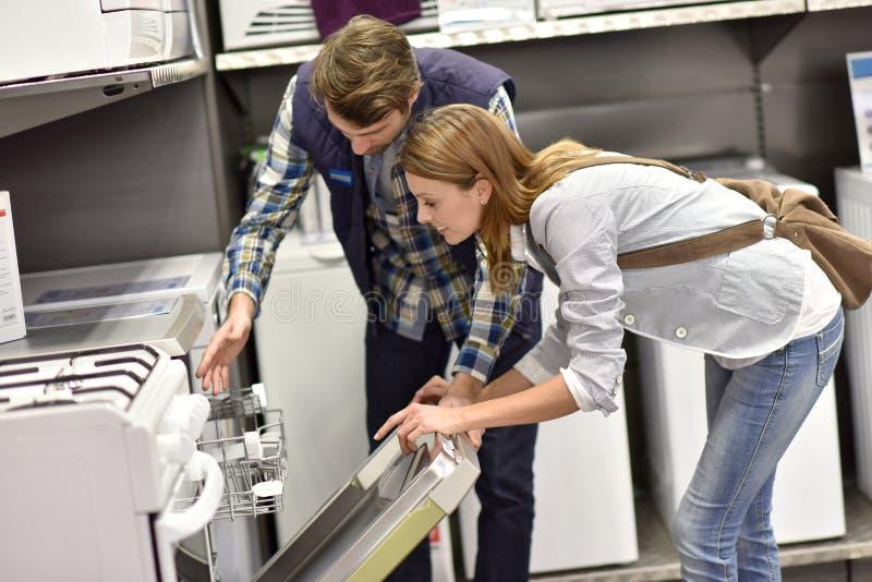 Vendedor que mostra a máquina de lavar louça da jovem mulher fotos de stock