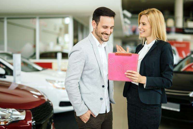 Vendedor que muestra el vehículo al cliente potencial foto de archivo libre de regalías