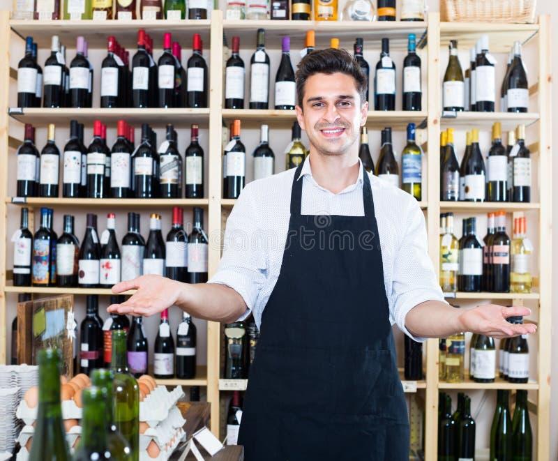 Vendedor que se coloca en la sección del alcohol imagen de archivo libre de regalías