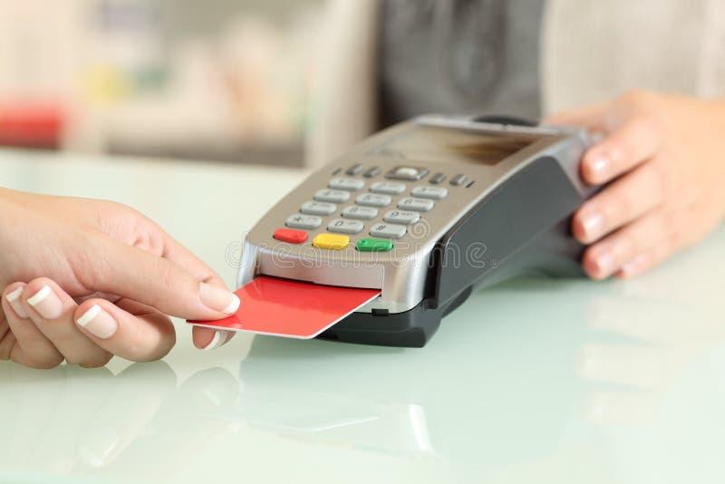 Vendedor que usa un dataphone para encargar de la tarjeta de crédito fotografía de archivo libre de regalías
